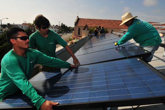 Solar City workers Tony Farias, left, Cody Corbett, middle, and Salvador Sanchez install solar panels onto the roof of St. Cross by the Sea Episcopal Church in Hermosa Beach. The church claims to be the first to use solar energy in the South Bay and expects to save thousands of dollars on their energy bills. (Steve McCrank/Staff Photographer)