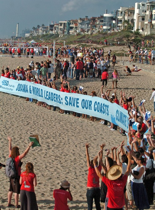 As part of the International Day of Climate Change on Saturday, participants line up and do the tidal wave for an airplane covering the event near the Manhattan Beach Pier. Organizers said 5,200 events were scheduled around the globe to mark the day. (Sean Hiller Staff Photographer)